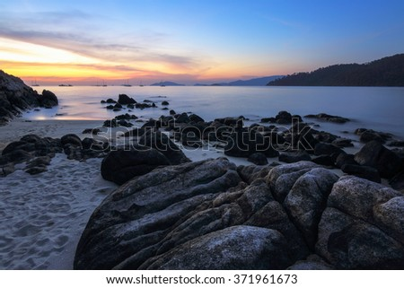 Silhouette rock on beach with sunset twilight