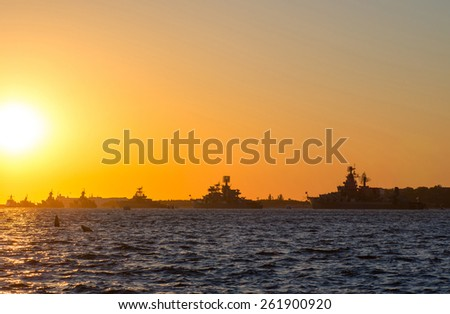 Silhouette row of warships in the Bay of Sevastopol against the setting sun - stock photo