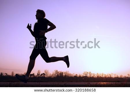 Silhouette runner in sunset rise - stock photo