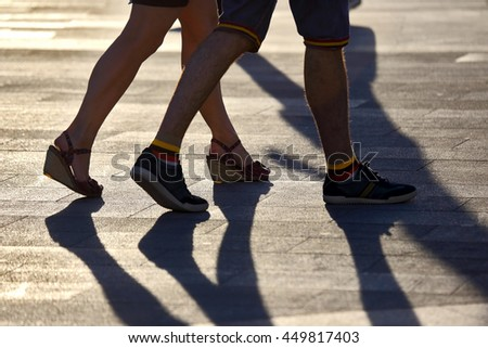 silhouette running two pairs of legs in back light sunlight