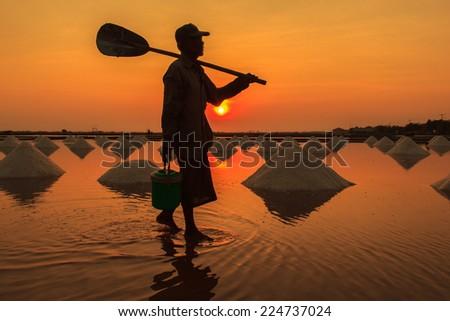 Silhouette Salt farming in the coastal Phetchaburi provinces of Thailand, Edit warm tone. - stock photo