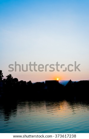 silhouette shot image of tree and sunset sky in background. - stock photo