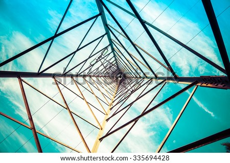 Silhouette shot of electricity pylons with cloudy sky - stock photo