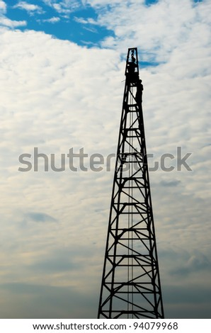 Silhouette shot of man on crane with dramatic sky.