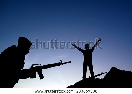 Silhouette shot of soldier holding gun - stock photo