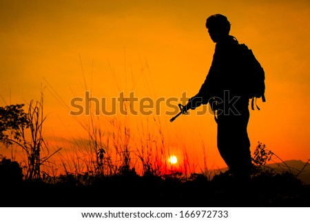 Silhouette shot of soldier holding gun with colorful sky and  mountain in background