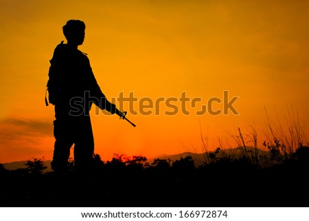 Silhouette shot of soldier holding gun with colorful sky and  mountain in background - stock photo
