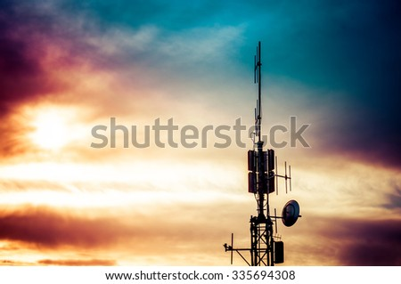 Silhouette shot of television and radio antenna pylon with cloudy sky - stock photo