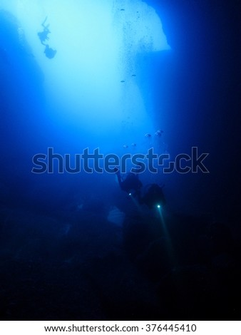 Silhouette shot of two divers holding torches entering a cave on Malta.