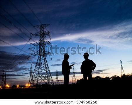 Silhouette Successful male engineer standing survey work on construction over blurred high-voltage pylons and construction. examination, inspection, survey - stock photo