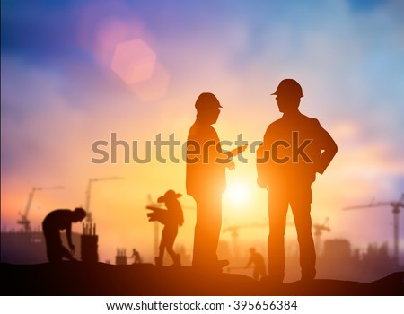 Silhouette Successful male engineer standing survey work on construction over blurred Worker in  construction site and nature