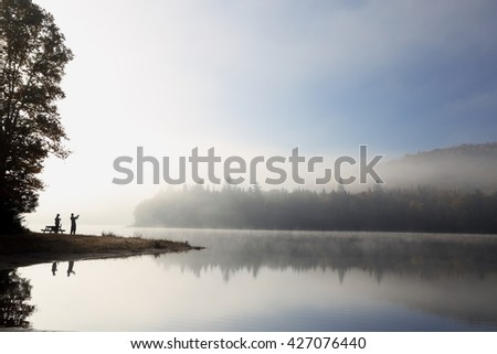 Silhouette. Sunrise on the lake. People silhouettes. Autumn landscape. Autumn landscape with colorful forest. Colorful autumn landscape. Autumn forest reflected in water.  - stock photo