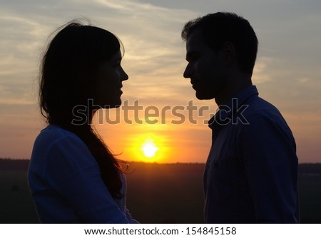 Silhouette sweethearts at sunset - stock photo