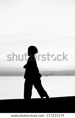 Silhouette taekwondo boy on the beach at dusk. Black and whit picture. - stock photo