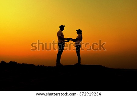silhouette teenager lovers couple over natural background at the beach and mountain:black shadow loving people hug and kiss:love and valentines concept:matrimonial/amour/affection/wedding/anniversary - stock photo