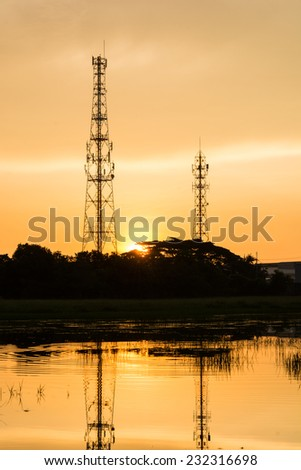 Silhouette telecommunications towers on sunrise reflection on river - stock photo