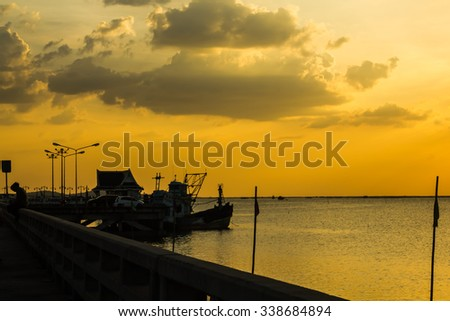Silhouette the bridge and pavilion and boat on Beautiful evening sunset above the sea and boat background. At Chonburi sea Thailand