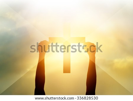 Silhouette the cross in hands, religion symbol in light and landscape over a sunrise, background, religious, faith concept - stock photo