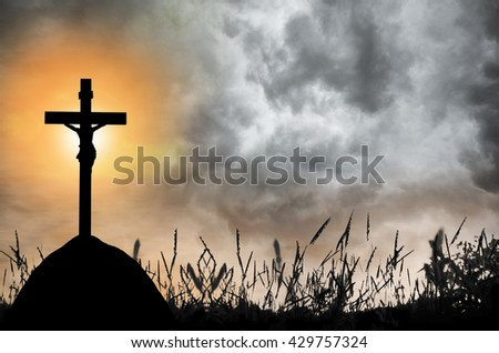 Silhouette the cross over blurred sunset and cloud storm background. - stock photo