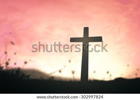 Silhouette the cross over over blurred beautiful sunset with amazing light background. - stock photo