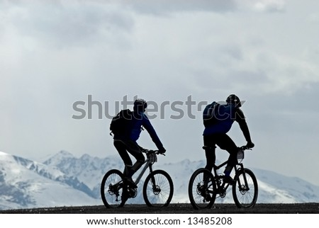 Silhouette two mountain bikers and snow peaks - stock photo