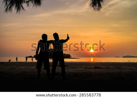 Silhouette Two young men on the beach having party, drinking and having a lot of fun in the sunset - stock photo