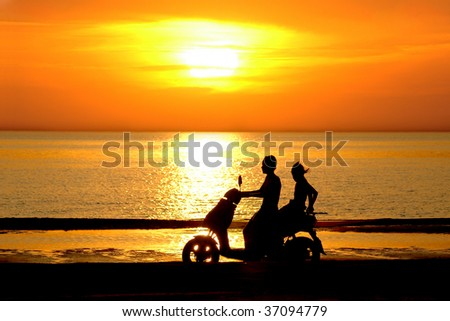 Silhouette two young people go on motor scooter on sundown