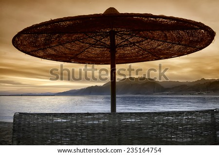 Silhouette umbrella at the beach and sunset. Red Sea. Egypt - stock photo