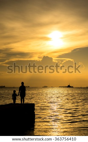 Silhouette unrecognized mother and her child together at bridge under sunset golden evening sky in Thailand