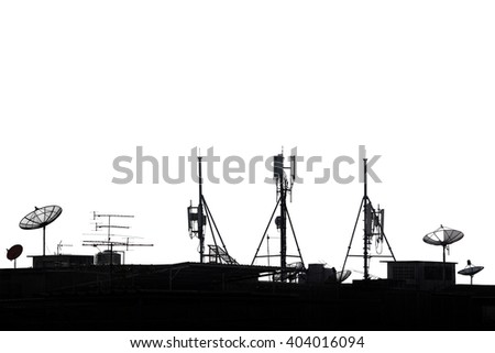 Silhouette various communication devices on rooftop; cell site, satellite receiver, TV antenna - stock photo