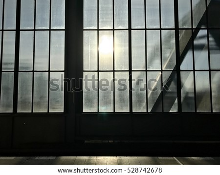Silhouette view from inside the building of Metro station through the window face the sun