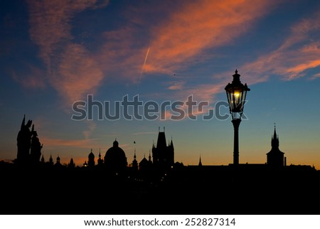 Silhouette view of Charles Bridge with its street lamps and statues and the old city of Prague at dawn (dramatic dawn lighting) - stock photo