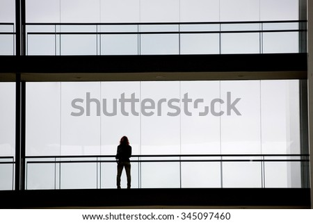 Silhouette view of young businesswoman in a modern office building interior with panoramic windows. - stock photo