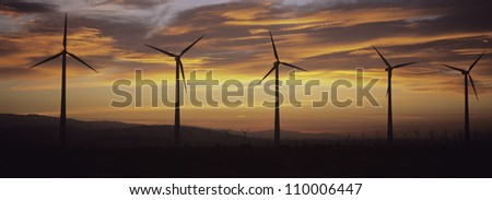 Silhouette wind turbines in a row against cloudy sky at sunset