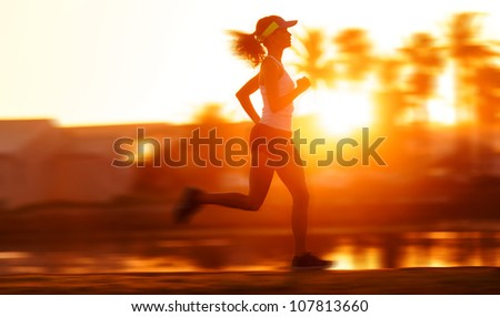 silhouette with motion blur of a woman athlete running at sunset or sunrise. fitness training of marathon runner. - stock photo