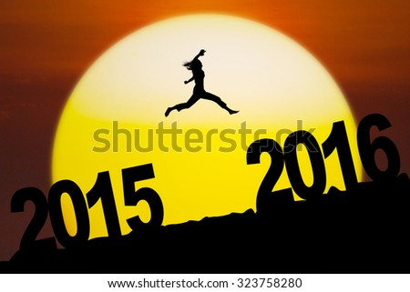 Silhouette woman jumping above numbers 2016 on the hill at sunset time. New year concept - stock photo