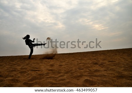 silhouette woman on sand, blurred and low key