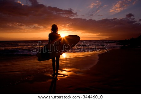 silhouette woman on tropical beach holding surfboard at sunset in maui