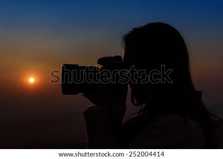 Silhouette woman photographer in dawn light