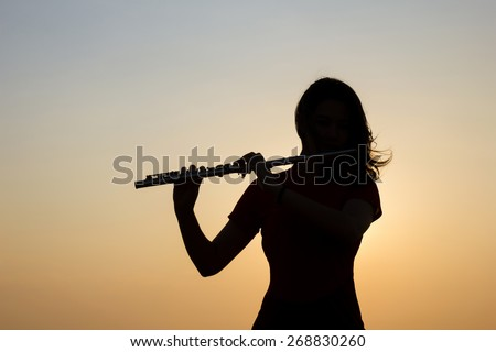Silhouette woman playing flute in sunset sky background. - stock photo