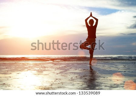 Silhouette woman practicing yoga on the beach at sunset