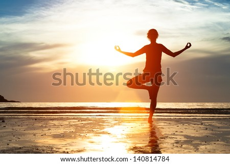Silhouette woman practicing yoga on the beach at sunset. - stock photo