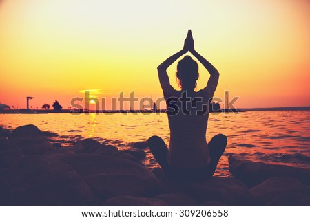 Silhouette woman practicing yoga posing on beach at sunset