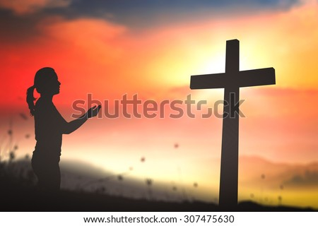 Silhouette woman praying over the cross on beautiful sunset with amazing light background. Worship, Forgiveness, Humble, Evangelical, Reconcile, Adoration, Glorify, Redeemer, Thanksgiving concept.