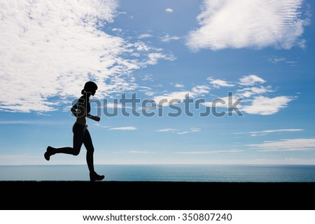 silhouette woman running on blue sea and blue sky background