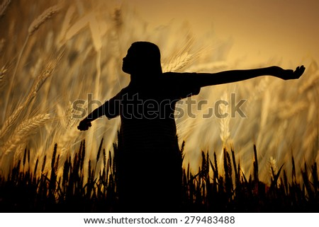 silhouette woman stands in a field of ripe wheat background - stock photo