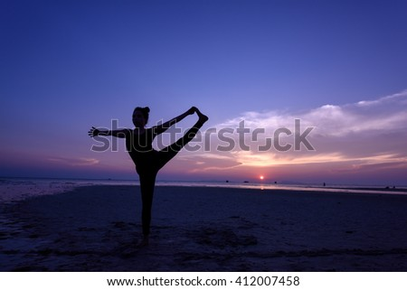 Silhouette woman with yoga posture on the beach at sunset