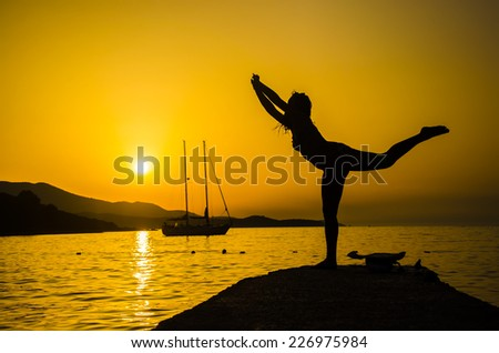Silhouette woman with yoga posture on the beach at sunset with sail boat yacht at background - stock photo