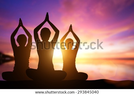 Silhouette woman yoga on the beach at sunset. - stock photo