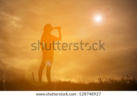 Silhouette women drinking water after running at the sky sunset, color of vintage tone